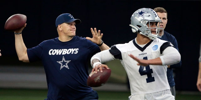 FILE - In this Wednesday, May 22, 2019 file photo, Dallas Cowboys quarterbacks coach Jon Kitna throws the ball alongside Dak Prescott (4) during NFL football practice in Frisco, Texas. Jon Kitna is back in the NFL with one of the quarterback's former teams in the Dallas Cowboys after coaching high school football for seven years. Kitna's return has plenty to do with his strong relationship with coach Jason Garrett. (AP Photo/Michael Ainsworth, File)