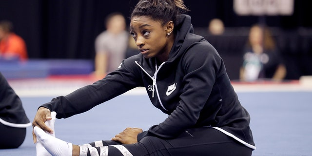 Simone Biles stretches during practice for the U.S. Gymnastics Championships Wednesday, Aug. 7, 2019, in Kansas City, Mo. (AP Photo/Charlie Riedel)