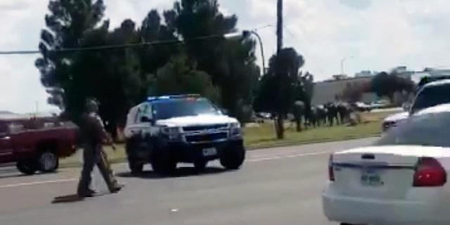 Police officers guarding a street in Odessa, Texas, on Saturday. (Dustin Fawcett via AP)