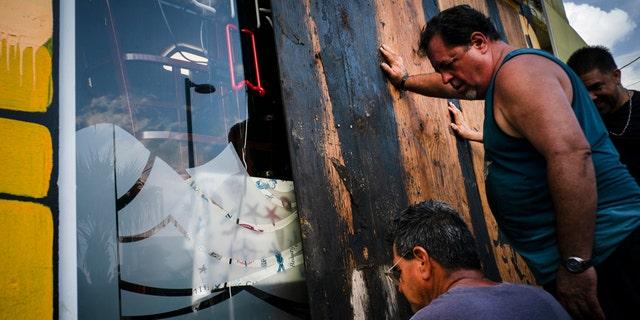 Men board up a shop's windows ahead of the arrival of Tropical Storm Dorian in Boqueron, Puerto Rico, Tuesday, Aug. 27, 2019.
