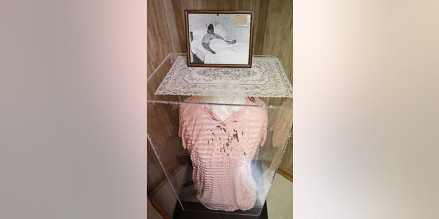 EDS NOTE: GRAPHIC CONTENT - In this Aug. 9, 2019, photo a photograph of Rhoda Wise and the dress she wore in the photo when she suffered the phenomenon of stigmata, bloody wounds on her head, hands and feet like those Jesus suffered on the Cross, is displayed in Canton, Ohio. Late in the summer of 1939, crowds of strangers started showing up at Rhoda Wise's house next to a city dump in Ohio after she let it be known that miracles were occurring in her bedroom. Seven decades later, people still make pilgrimages to the wood frame bungalow at the edge of Canton seeking their own miracles.