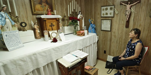 In this Aug. 9, 2019, photo Marge Ruminski, from Parma, Ohio, sits in the chair where Rhoda Wise was visited by Jesus Christ in front of the altar in Canton, Ohio.