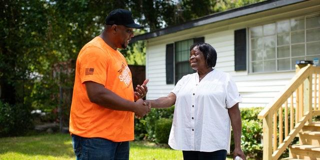Robert Bogus III speaks with homeowner Beatrice Richard after Team Patriot members repaired her Houston, Texas home.
