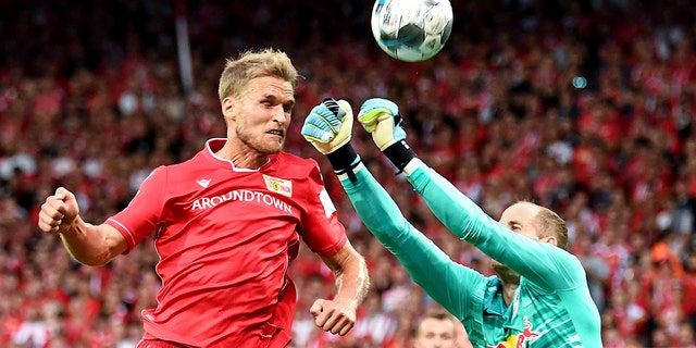 Berlin's Sebastian Andersson, left, vies for the ball with Leipzig goalkeeper Peter Gulacsi, during the German Bundesliga soccer match between Union Berlin and RB Leipzig, at the Stadion An der Alten Foersterei, in Berlin, Sunday, Aug. 18, 2019. (Britta Pedersen/dpa via AP)