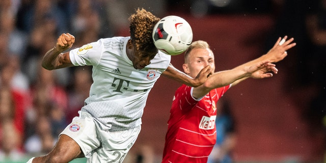 Munich's Kingsley Coman, left, and Tobias Hasse from Cottbus challenge for the ball during the German soccer cup, DFB Pokal, first Round match between FC Energie Cottbus and FC Bayern Munich in Cottbus, Germany, Monday, Aug. 12, 2019. Foto: Robert Michael/dpa via AP)