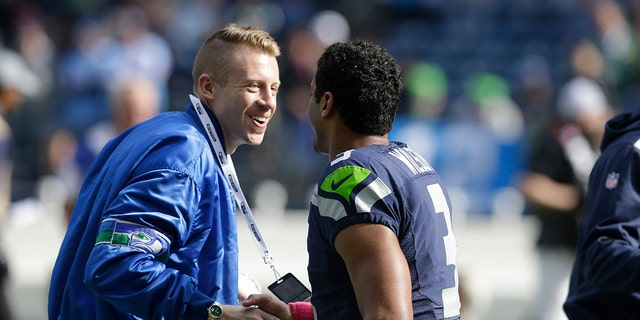 FILE - In this Oct. 13, 2013, file photo, Seattle hip hop and rap singer Macklemore, left, greets Seattle Seahawks quarterback Russell Wilson before an NFL football game between the Seahawks and Tennessee Titans in Seattle. The MLS soccer Seattle Sounders team announced Tuesday, Aug. 13, 2019, that they are adding Macklemore and Wilson to club's ownership group, along with several others as Hollywood producer Joe Roth leaves the franchise.(AP Photo/Elaine Thompson, File)