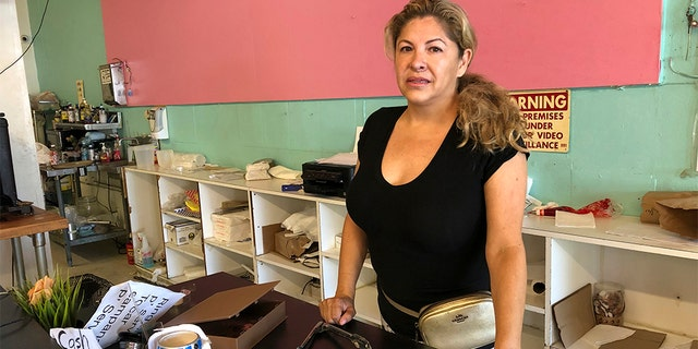 Dona Beltran, owner of M Bakery is seen behind her bakery counter in Garden Grove, Calif., Thursday, Aug. 8, 2019. She said the suspect came in late Wednesday afternoon and took the entire cash register. She said she ran to a nearby dental office to safety when she saw she was being robbed.