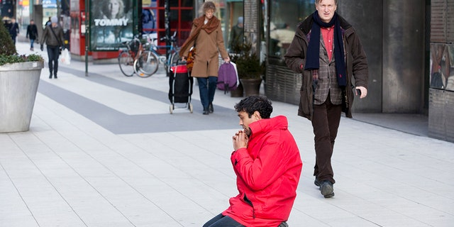 A man begs on a busy commercial street, on March 11, 2014 in Stockholm, Sweden.
