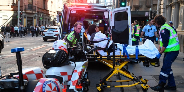 A women is taken by ambulance from Hotel CBD at the corner of King and York Street in Sydney, Australia Tuesday, Aug. 13, 2019.