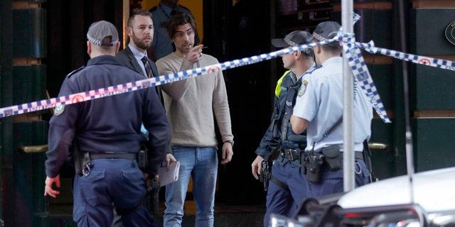 A man, center, points as he assists police at a building where a person has been found dead after a man attempted to stab multiple people in Sydney, Australia, Tuesday, Aug. 13, 2019.