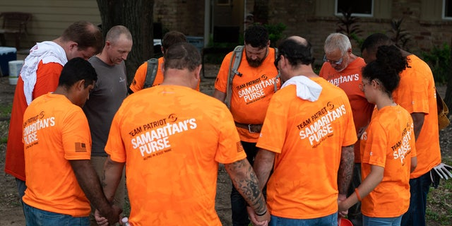 Team Patriot members pray after a day spent installing bathrooms, repairing windows and laying trim at a home devastated by Hurricane Harvey.
