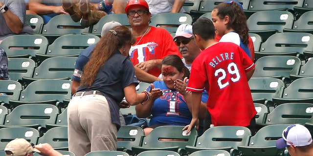 A fan reacts after being stuck in the forehead by a foul ball off the bat of Willie Calhoun #5 of the Texas Rangers as the Rangers play the Detroit Tigers during the first inning at Globe Life Park in Arlington on August 4, 2019 in Arlington, Texas. (Photo by Ron Jenkins/Getty Images)