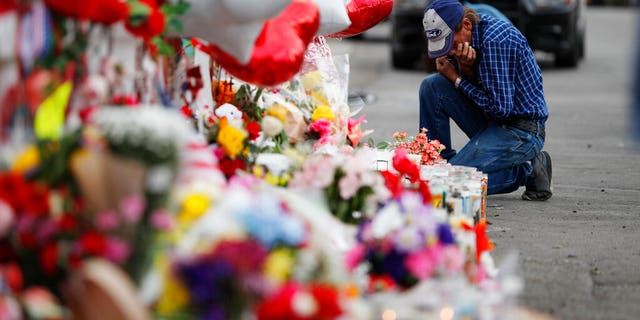 A man cries beside a cross at a makeshift memorial near the scene of a mass shooting at a shopping complex Tuesday, Aug. 6, 2019, in El Paso, Texas. (AP Photo/John Locher)