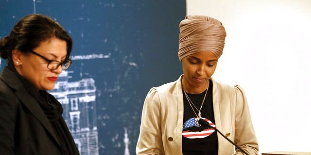 Rep. Ilhan Omar, D-Minn., right, and Rep. Rashida Tlaib, D-Mich., take a quiet moment as they talked about Israel's refusal to allow them to visit the country during a news conference Monday, Aug. 19, 2019 at the State Capitol in St. Paul, Minn. (AP Photo/Jim Mone)