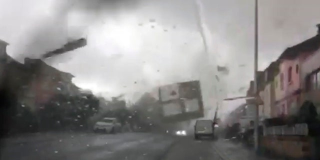 A tornado hurls objects, including doors and roofs, through the air, as seen from inside a car with a cracked windshield, in Pettingen, Luxembourg, Friday Aug. 9, 2019.