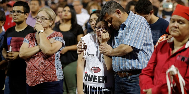 People comfort each other during a vigil for victims of Saturday's mass shooting at a shopping complex Sunday, Aug. 4, 2019, in El Paso, Texas.