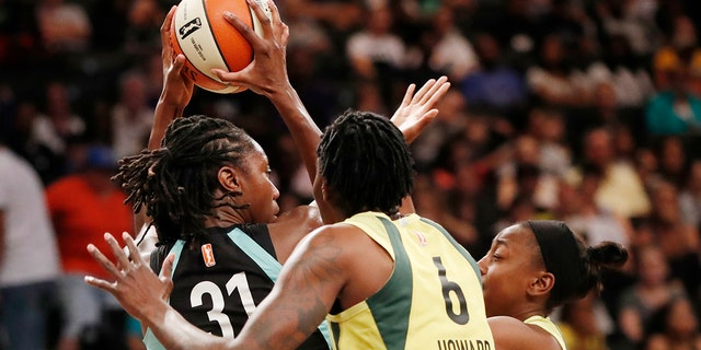 Seattle Storm forward Natasha Howard, right, defends New York Liberty center Tina Charles, left, who looks to pass during the first half of a WNBA basketball game, Sunday, Aug. 11, 2019, in New York. (AP Photo/Kathy Willens)