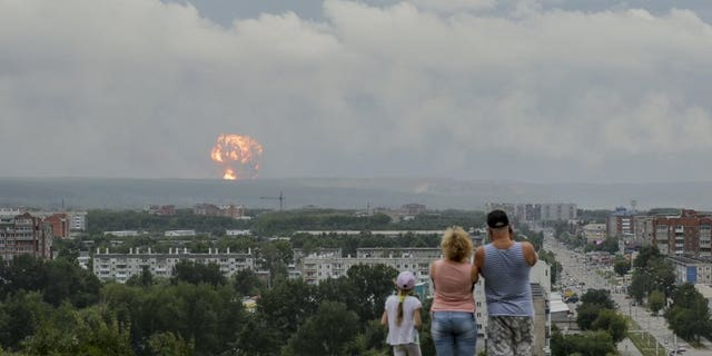 In this photo taken on Monday, Aug. 5, 2019, a family watches explosions at a military ammunition depot near the city of Achinsk in eastern Siberia's Krasnoyarsk region, in Achinsk, Russia. Russian officials say powerful explosions at a military depot in Siberia left 12 people injured and one missing and forced over 16,500 people to leave their homes.