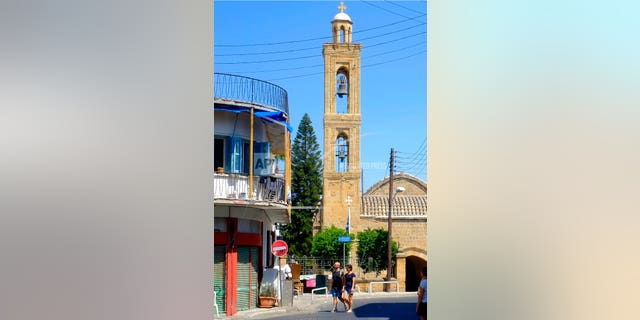 Tourist walk in the old city by a Christian Orthodox church in downtown Nicosia, Cyprus, Thursday, Aug. 1, 2019. Cyprus' attorney general says he has instructed police to launch an investigation into whether an Orthodox Christian bishop has committed a criminal offense over his remarks on homosexuals.