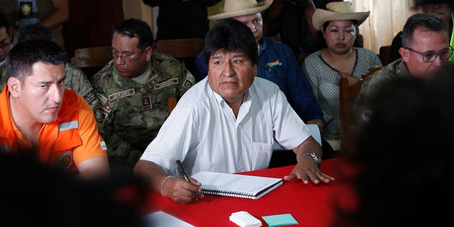 Bolivia's President Evo Morales, center, sits next to his Defense Minister Javier Zavaleta, left, during a meeting to discuss firefighting efforts in Robore, Bolivia, Tuesday, Aug. 27, 2019.