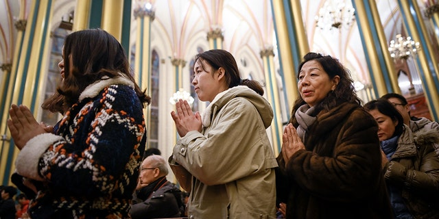 Chinese worshippers attend a Mass during Christmas Eve at a Catholic church in Beijing on December 24, 2018. (Photo by WANG ZHAO / AFP) (Photo credit should read WANG ZHAO/AFP/Getty Images)