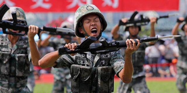 FILE - In this June 30, 2019, file photo, soldiers of Chinese People's Liberation Army (PLA) demonstrate their skill during an open day of Stonecutter Island naval base, in Hong Kong, to mark the 22nd anniversary of Hong Kong handover to China.