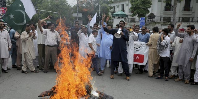 Pakistani clerks shout anti-India slogans after burning effigies of Indian Prime Minster Narendra Modi during a protest to express support and solidarity with Indian Kashmiri people in their peaceful struggle for their right to self-determination, in Lahore, Pakistan, Tuesday, Aug. 6, 2019.