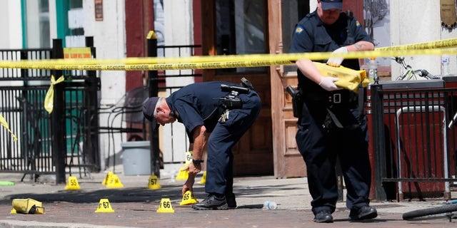 Authorities retrieve evidence markers at the scene of a mass shooting, Sunday, Aug. 4, 2019, in Dayton, Ohio.