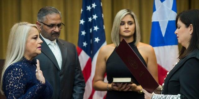 Justice Secretary Wanda Vazquez is sworn in as governor of Puerto Rico by Supreme Court Justice Maite Oronoz Wednesday in San Juan. (AP Photo/Dennis M. Rivera Pichardo)