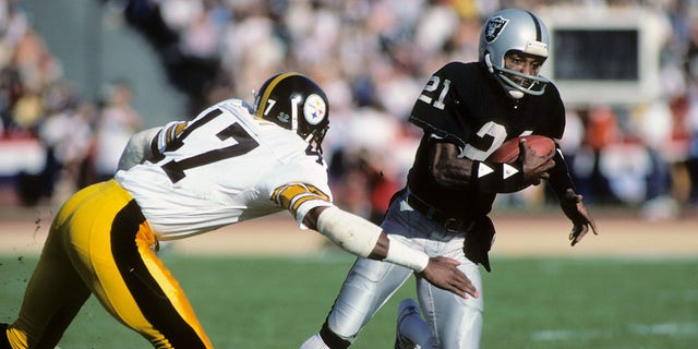 Cliff Branch, right, of the then-Los Angeles Raiders, runs the ball against Mel Blount of the Pittsburgh Steelers during an AFC playoff game in Los Angeles, Jan. 1, 1984. (Getty Images)