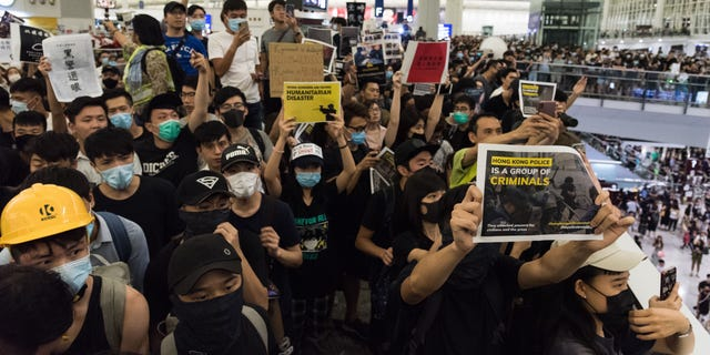 Protesters hold placards during a demonstration at the Hong Kong International Airport.  (Photo by Aidan Marzo/SOPA Images/LightRocket via Getty Images)