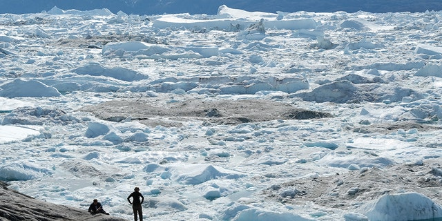 Visitors look out onto free-floating ice jammed into the Ilulissat Icefjord during unseasonably warm weather on July 30, 2019 near Ilulissat, Greenland. The Sahara heat wave that recently sent temperatures to record levels in parts of Europe is arriving in Greenland. (Photo by Sean Gallup/Getty Images)