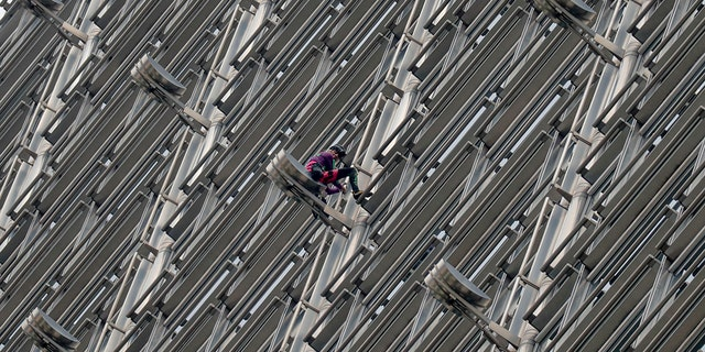 Alain Robert, a French rock and urban climber hangs on to Cheung kong centre building after hanging a large fabric displaying Chinese and Hong Kong flags, shaking hands and shining sun in Hong Kong, Friday, Aug. 16, 2019. (AP Photo/Vincent Thian)