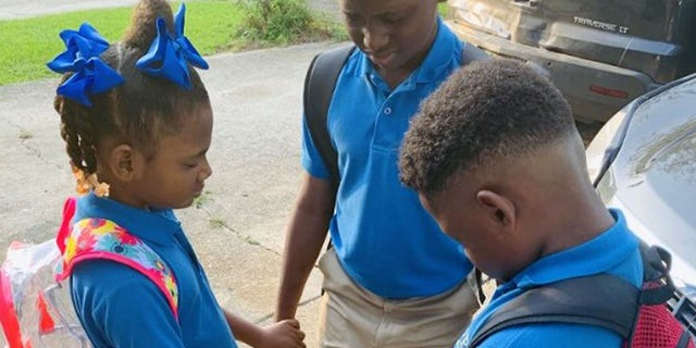 Jamisha Harris shared a photo of her children Eugene Jacobs, 10, Jorden Jacobs, 8, and Emily Jacobs, 7, praying before their first day of school.
