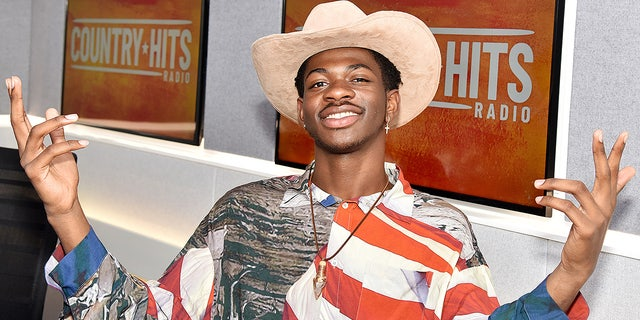 "Lil Nas X visits the Country Hits Radio studios on July 04, 2019 in London. The rapper's smash ""Old Town Road"" has CMA Awards voters divided on whether it's ""country"" enough to qualify for a trophy."