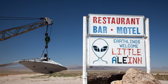 Sign for Little A'Le'Inn and flying saucer hanging from tow truck, Rachel, Nevada, near Area 51.