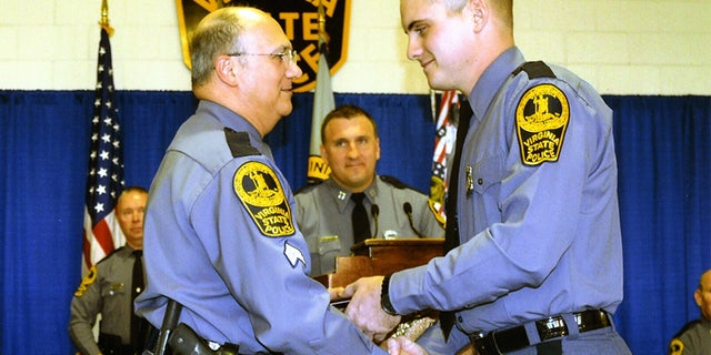 Sgt. Bob Carpentieri presenting Lucas Dowell his graduation certificate from the Virginia State Police academy.