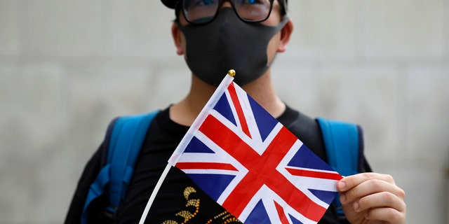 A supporter holds a British flag outside of the British Consulate in Hong Kong during a rally in support of an employee of the consulate who was detained while returning from a trip to China, Wednesday, Aug. 21, 2019.
