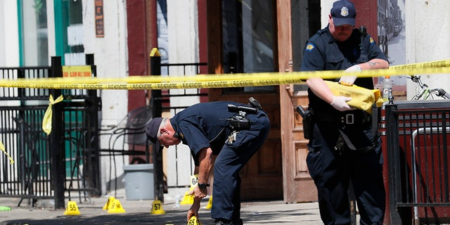 Authorities retrieve evidence markers at the scene of a mass shooting in Dayton, Ohio.