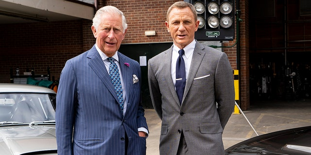 Prince Charles, Prince of Wales poses with British actor Daniel Craig as he tours the set of the 25th James Bond Film at Pinewood Studios on June 20, 2019 in Iver Heath, England.