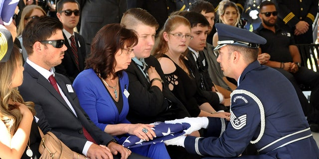 An American flag is presented to McKeithen's wife, Pamela, during a service at the Biloxi National Cemetery. McKeithen was an Air Force veteran.