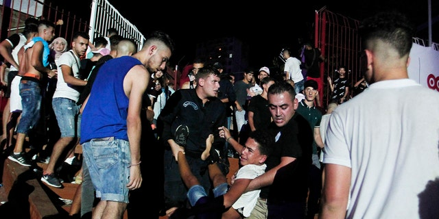 A man is evacuated during a concert by Algerian rap artist Abderraouf Derradji's, known as Soolking, at a stadium in Algiers, Thursday, Aug. 22, 2019. (AP Photo/Fateh Guidoum)
