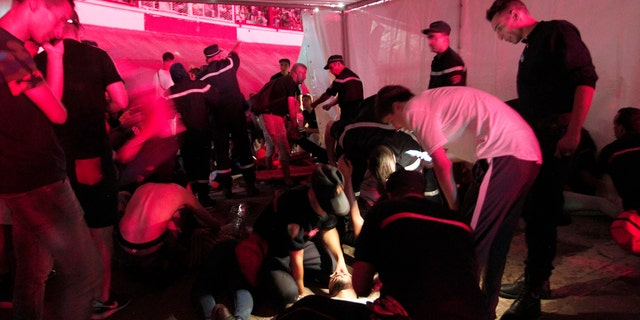 People are being tended by rescue workers during Algerian rap artist Abderraouf Derradji's concert, known as Soolking, at a stadium in Algiers, Thursday, Aug. 22, 2019. (AP Photo/Fateh Guidoum)