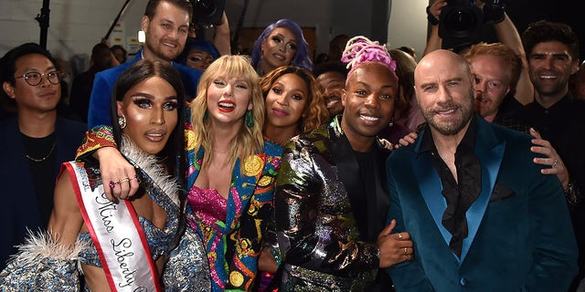 Taylor Swift, Todrick Hall, John Travolta, and Jesse Tyler Ferguson pose backstage during the 2019 MTV Video Music Awards at Prudential Center on Aug. 26, 2019 in Newark, New Jersey.