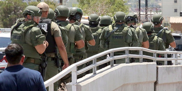 Law enforcement officers make their way along a walkway to the scene of a mass shooting at Walmart in El Paso, Texas. (AP)