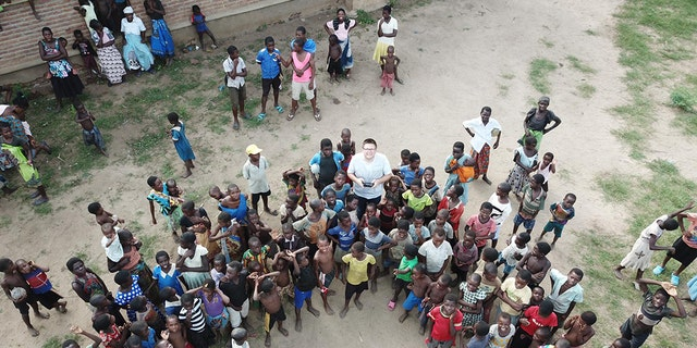 Crowd watches UNICEF Malawi's Drone Co-ordinator Tautvydas Juskauskas testing a drone