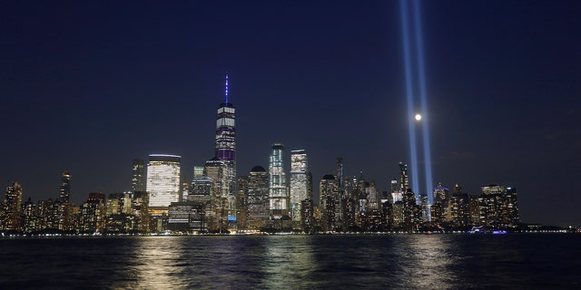 The moon passes through the annual Tribute in Light illuminated on the skyline of lower Manhattan on the 18th anniversary of the 9/11 attacks in New York City on Sept. 11, 2019 as seen from Jersey City, New Jersey. (Photo by Gary Hershorn/Getty Images)