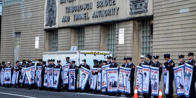 FDNY firefighters at the Tunnel to Towers race hold banners honoring fellow firefighters who were killed on 9/11. (Courtesy of Tunnel to Towers Foundation/Clare Photography)