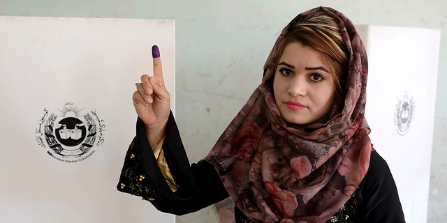 An Afghan woman shows her inked finger after casting her vote at a polling station in Kabul, Afghanistan, Saturday, Sept. 28, 2019. Afghans headed to the polls on Saturday to elect a new president amid high security and threats of violence from Taliban militants, who warned citizens to stay away from polling stations or risk being hurt. (AP Photo/Ebrahim Noroozi)