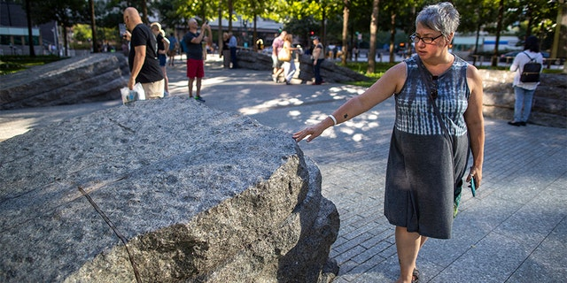 A visitor touches one of the granite slabs at the 9/11 Memorial Glade in New York City. When the names of nearly 3,000 Sept. 11 victims are read aloud today at the World Trade Center, a half-dozen stacks of stone will quietly salute an untold number of people who aren't on the list. (AP)